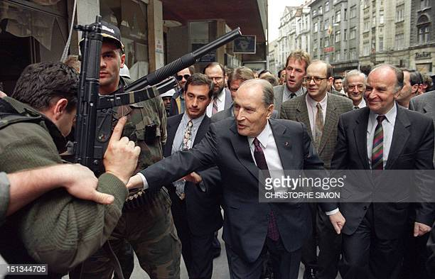 French President Francois Mitterrand is accompanied by his Bosnian counterpart Alija Izetbegovic as he greets Bosnian militiamen 28 June 1992 in...