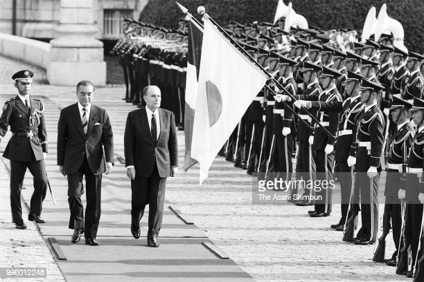 French President Francois Mitterrand reviews the honour guard with Japanese Prime Minister Yasuhiro Nakasone during the welcome ceremony ahead of the...