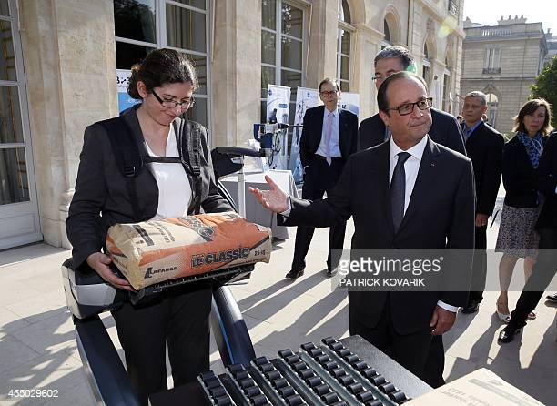 French President François Hollande looks at a person using an exoskeleton after the presentation of the '34 plans for the new industrial France' on...