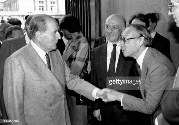 French President François Mitterrand shakes hands with Chinese American architect Ieoh Ming Pei as Louvre Museum director Michel Laclotte looks on...