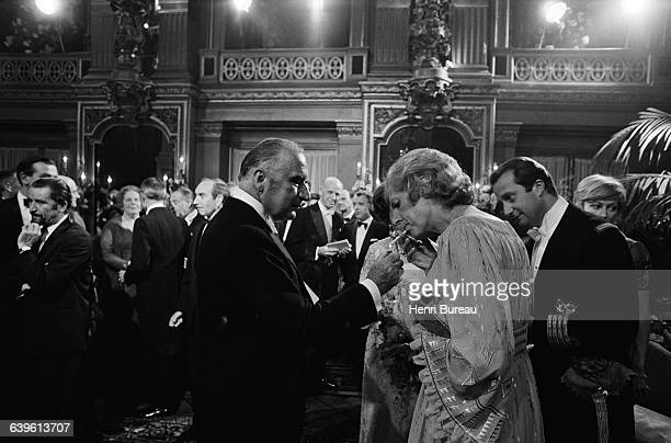 French President Georges Pompidou lights a cigarette for his wife Claude who accompanied him on an official visit to Belgium Behind her to the right...