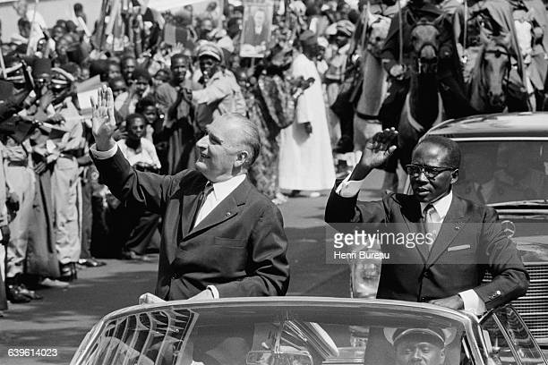 French President Georges Pompidou rides beside Senegalese President Leopold Sedar Senghor for a reception at the presidential palace in Dakar during...
