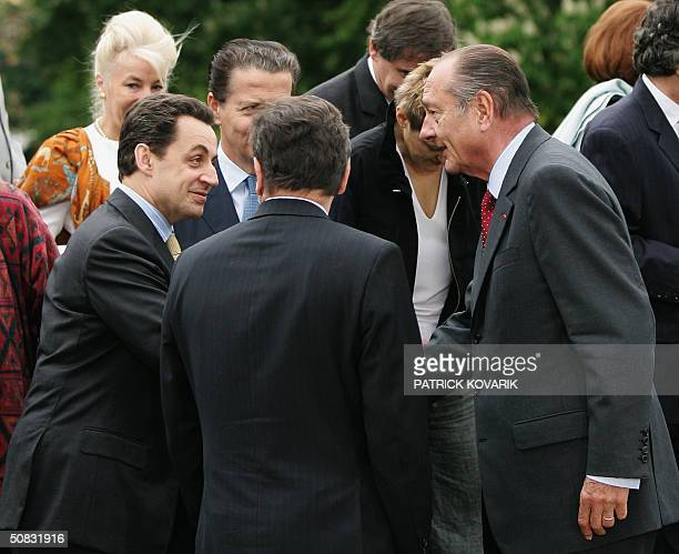 French president Jacques Chirac chats with French Economy minister Nicolas Sarkozy in the garden of the Elysee Palace 13 May 2004 in Paris after a...