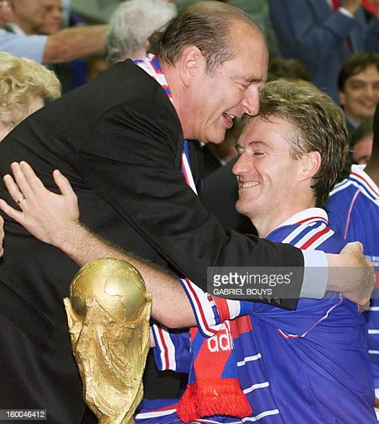 French President Jacques Chirac hugs French captain Didier Deschamps before handling him the FIFA trophy 12 July at the Stade de France in SaintDenis...