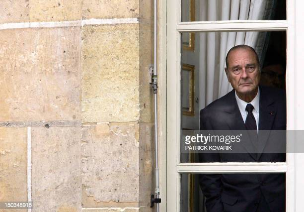 French President Jacques Chirac is seen through a window of the Elysee palace, 04 October 2005 in Paris, before posing for a picture with Italian...