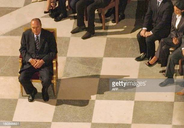 French President Jacques Chirac, left, attends a mass at Notre-Dame de Paris cathedral 26 August 2004 to attend a mass as part of the celebrations of...