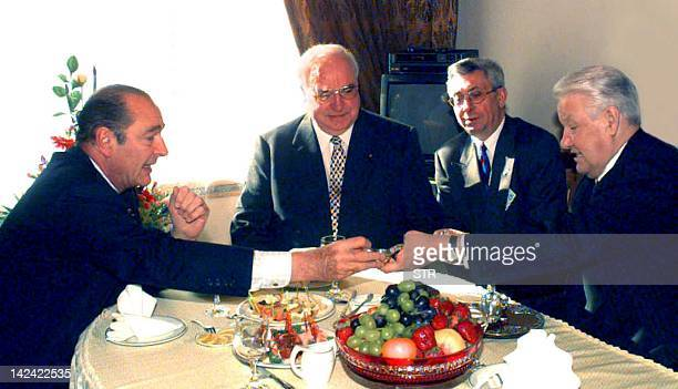 French President Jacques Chirac receives a souvenir gift from his Russian counterpart Boris Yeltsin as German Chansellor Helmut Kohl looks on during...