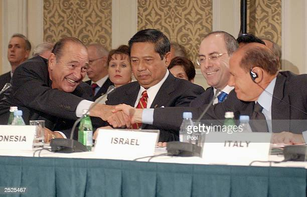 French President Jacques Chirac shakes hands with Italian Prime Minister Silvio Berlusconi at the conference on fighting terrorism which is focusing...