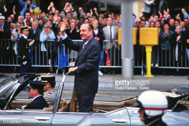 French President Jacques Chirac waves from a motorcade during the military parade celebrating Bastille Day on the Champs Elysees on July 14 1996 in...
