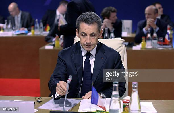 French President Nicolas Sarkozy adjusts his microphone before the first working session at the Group of 20 Cannes Summit at the Palais des Festivals...
