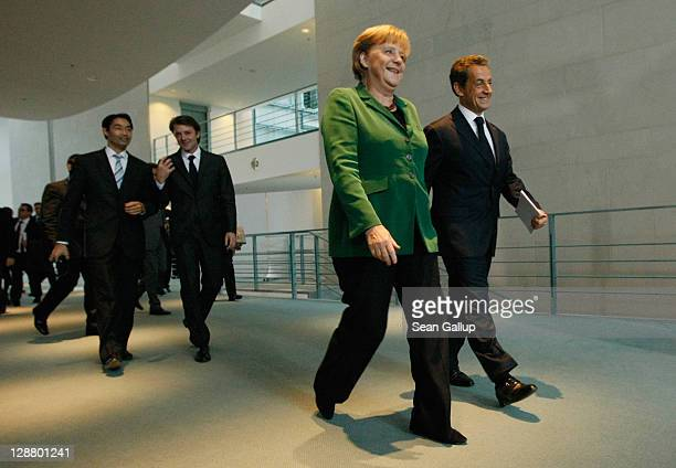 French President Nicolas Sarkozy and German Chancellor Angela Merkel, followed by French Finance Minister Francois Baroin and German Vice Chancellor...