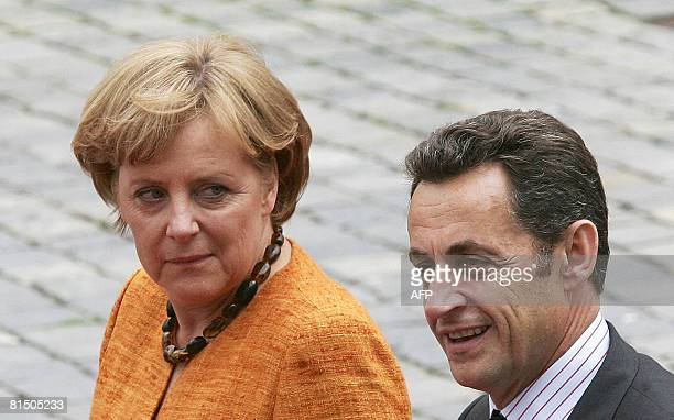 French President Nicolas Sarkozy and German Chancellor Angela Merkel walk together ahead of the French-German one-day summit June 9, 2008 in the...