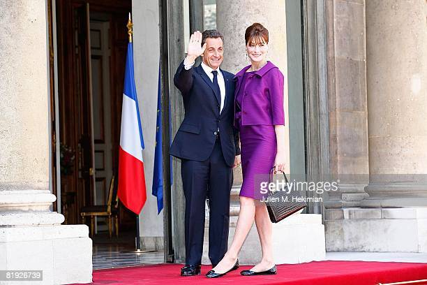 French President Nicolas Sarkozy and his wife Carla Bruni-Sarkozy arrive in the courtyard of the Elysee for the garden party following the Bastille...