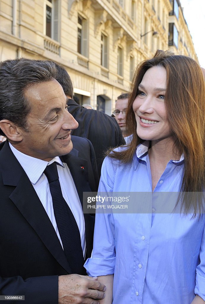 French President Nicolas Sarkozy (L) and his wife Carla Bruni-Sarkozy visit exhibitions on the Champs-Elysees in Paris, on May 24, 2010. The young French farmers' union organized a two-day event called 'Nature Capitale' where they installed the fields and forest of France in the French capital. The union, representing farmers under the age of 35, aim to showcase farm production from sheep breeding to crop growing and win public support for their embattled sector.