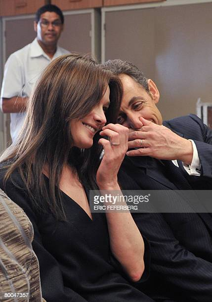 French President Nicolas Sarkozy and his wife Carla BruniSarkozy talk together during their visit to the Gugulethu AIDES institute with archibishop...