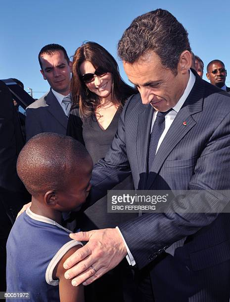 French President Nicolas Sarkozy and his wife Carla BruniSarkozy talk to a child in Gugulethu AIDS institute near Cape Town on February 28 2008...