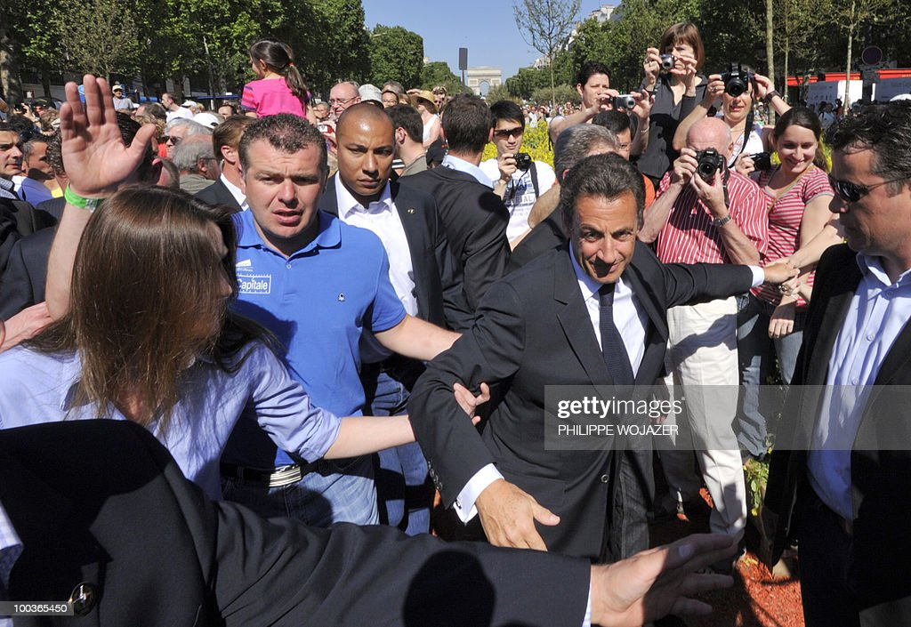 French President Nicolas Sarkozy (2ndR) and his wife Carla Bruni-Sarkozy (L) walk among the crowd as they visit exhibitions on the Champs-Elysees in Paris, on May 24, 2010. The young French farmers' union organized a two-day event called 'Nature Capitale' where they installed the fields and forest of France in the French capital. The union, representing farmers under the age of 35, aim to showcase farm production from sheep breeding to crop growing and win public support for their embattled sector.