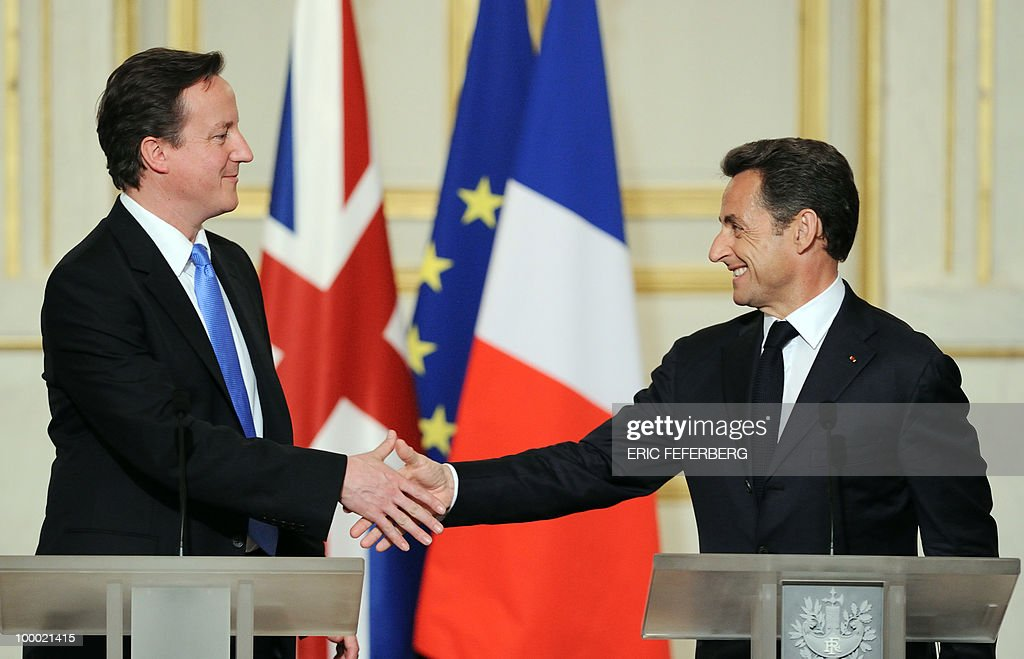 French President Nicolas Sarkozy (R) and the new Britain's Prime Minister David Cameron shake hands at the end of the press conference following their diner at the Elysee Palace on May 20, 2010 in Paris. Cameron and his coalition deputy unveiled full details today of their 'historic' power-sharing deal, under growing scrutiny for signs of strain.