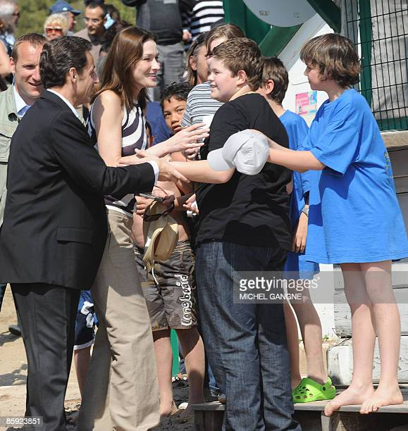 French President Nicolas Sarkozy and wife First Lady Carla BruniSarkozy are greeted by children before attending the trophy ceremony of the first...