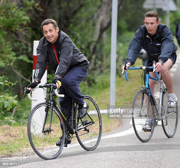 French president Nicolas Sarkozy arrives on his bike his wife Carla BruniSarkozy's residency on April 12 2009 in the French city of Cavaliere where...