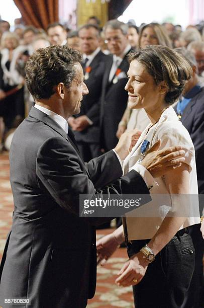 French president Nicolas Sarkozy awards French deputy minister for Ecology Chantal Jouanno chevalier de l'Ordre national du Merite on June 30 2009 at...