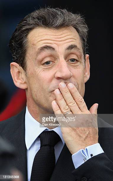 French President Nicolas Sarkozy blows a kiss on his arrival to the conference centre for the second day of the G20 Summit on November 4 2011 in...