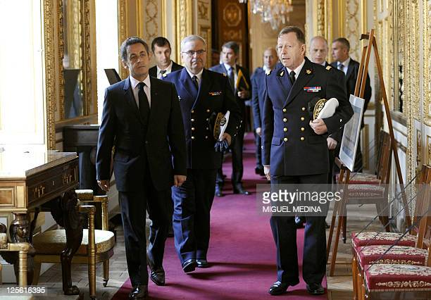 French President Nicolas Sarkozy flanked by Marine Headquarters Chief Admiral Rogel and general commissioner delegated to the Marine heritage Olivier...