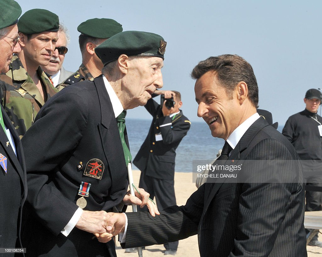 French President Nicolas Sarkozy (C), flanked by Prime Minister Francois Fillon (R) shakes hands with Maurice Chauvet, (L), member of the Kieffer commando, on May 8, 2008 as part of ceremonies commemorating the armistice of May 8, 1945, in Ouistreham, Normandy, western France, for the 63rd anniversary of the Allied victory over Nazi Germany in World War II. The special forces of French Captain Philippe Kieffer landed on June 6, 1944 on the beach of Ouistreham during the WWII allied forces D-Day. The special forces of French Captain Philippe Kieffer landed on June 6, 1944 on the beach of Ouistreham during the WWII allied forces D-Day.