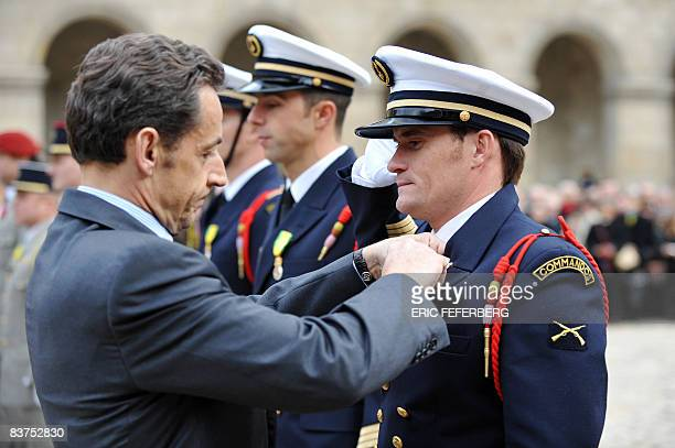 French president Nicolas Sarkozy gives a military medal to Gaetan Nogues member of the commando Hubert during the Fall military ceremony on November...