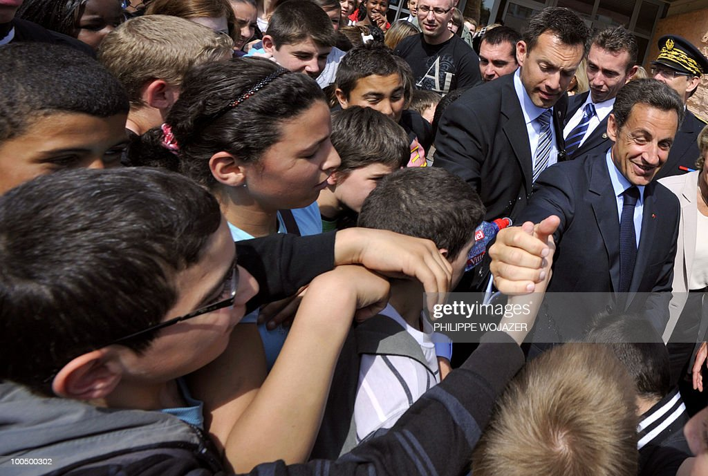 French President Nicolas Sarkozy (R) greets pupils as he arrives at the Charles Fauqueux college after a meeting on school violences and truancy, on May 25, 2010 in Beauvais, northern France.