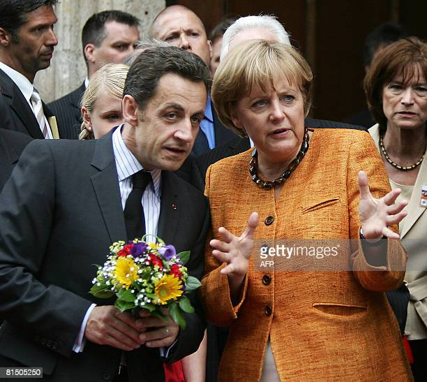 French President Nicolas Sarkozy holds a bouquet of flowers and talks with German Chancellor Angela Merkel ahead of the French-German one-day summit...
