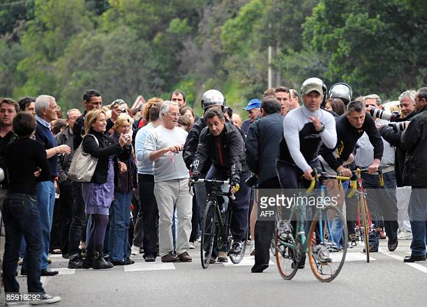 French president Nicolas Sarkozy is on his bike surrounded by people as he leaves his wife Carla BruniSarkozy's residency on April 12 2009 in the...