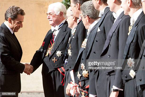 French President Nicolas Sarkozy is received by Vatican officials at the San Damaso courtyard prior a meeting with Pope Benedict XVI at the Vatican