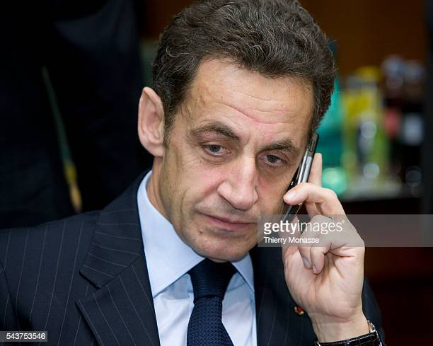 French President Nicolas Sarkozy is talking on the phone prior to the start of the EU Summit