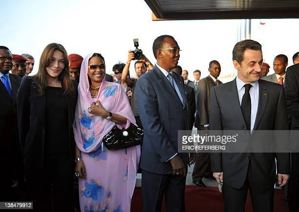 French President Nicolas Sarkozy is welcomes by his Chadian counterpart Idriss Deby as his wife Carla poses with Chad first Lady Hinda Deby upon...