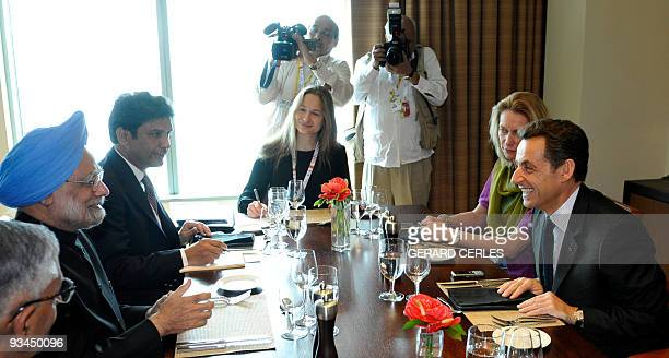 French President Nicolas Sarkozy jokes with Indian President Mammohan Singh prior to a working lunch on the sideline of the Commonwealth Climate...