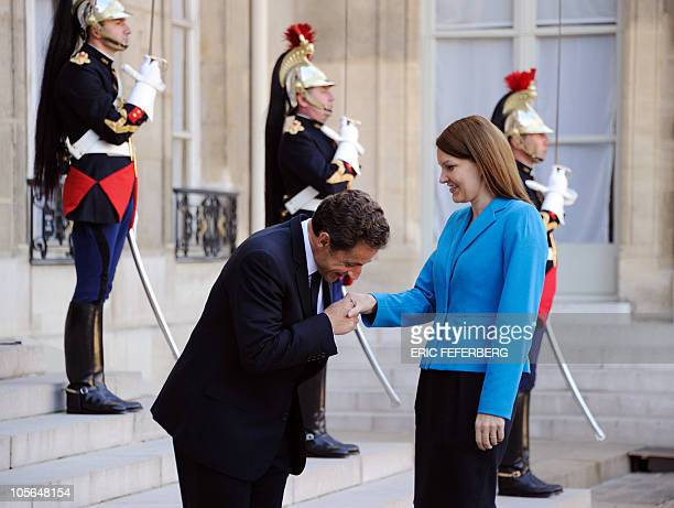 French President Nicolas Sarkozy kisses Finland Prime minister Mari Kiviniemi's hand as she arrives for a meeting on October 13 2010 at the Elysee...