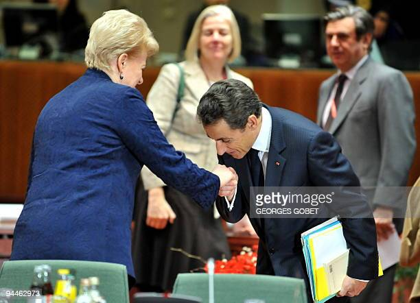 French President Nicolas Sarkozy kisses Lithuanian President Dalia Grybauskaite prior to a working session at an European Union summit at the...
