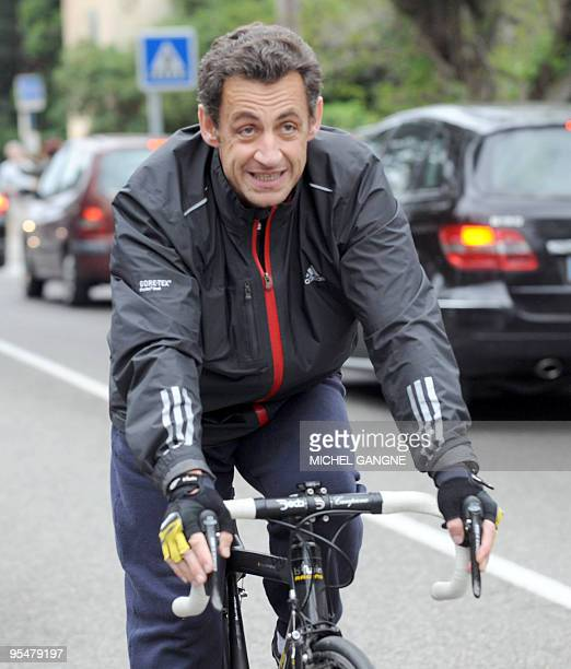 French president Nicolas Sarkozy leaves on his bike his wife Carla BruniSarkozy's residency on April 12 2009 in the French city of Cavaliere where...