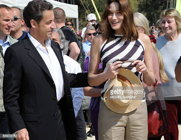 French President Nicolas Sarkozy looka at his wife First Lady Carla BruniSarkozy upon arrival with Carla Sarkozy's mother Marisa BruniTedeschi to...