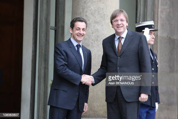 French president Nicolas Sarkozy receives a book by Belgian painter Pierre Alechinsky from Belgium's Prime Minister Guy Verhofstadt during a meeting...