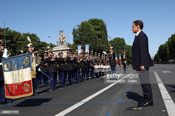 French President Nicolas Sarkozy reviews troops prior to the Bastille Day parade on the Champs Elysee in Paris