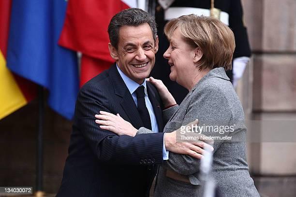 French President Nicolas Sarkozy says goodbye to German Chancellor Angela Merkel prior to a meeting with Italian Prime Minister Mario Monti on...