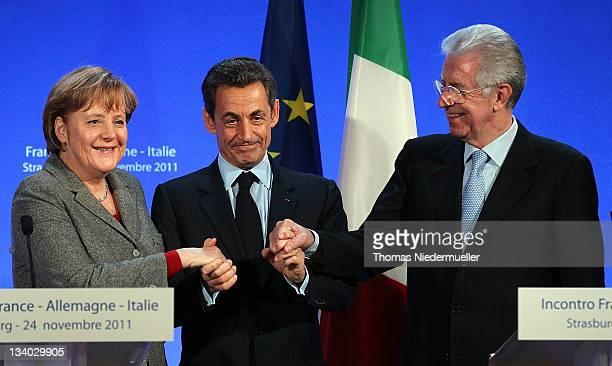 French President Nicolas Sarkozy shake hands with German Chancellor Angela Merkel and Italian Prime Minister Mario Monti on November 24, 2011 in...
