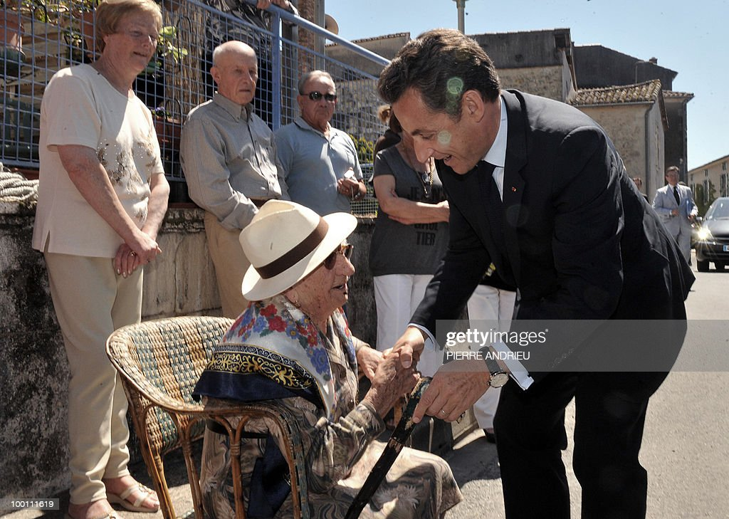 French President Nicolas Sarkozy (R) shakes hands with a woman after visiting a local farm, on May 21, 2010 in Bouglon, southwestern France, during his visit in the region.