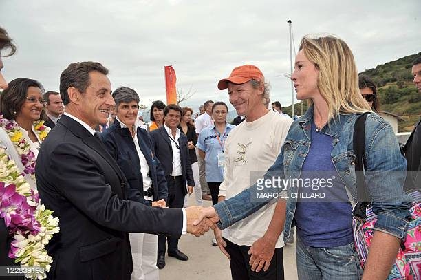 French President Nicolas Sarkozy shakes hands with French actress Geraldine Danon flanked by her husband French sailor Philippe Poupon on August 27...