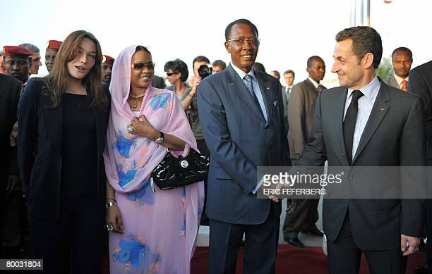 French President Nicolas Sarkozy shakes hands with his Chad's counterpart Idriss Deby Itno as his wife Carla BruniSarkozy talks with Chad first lady...