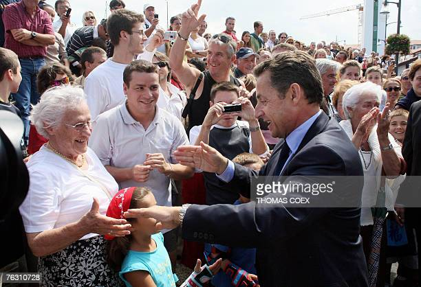 French president Nicolas Sarkozy shakes hands with tourists before having lunch in the French Basque city of Ciboure southwestern France 24 August...