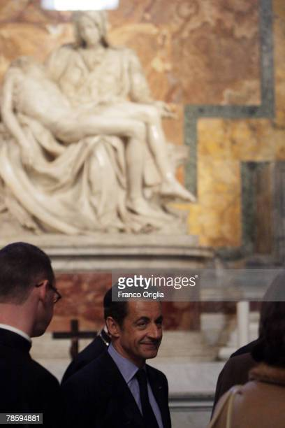 French President Nicolas Sarkozy stops in front of the marble statue The 'Pieta', by Michelangelo, during a visit to St. Peter's Basilica on December...