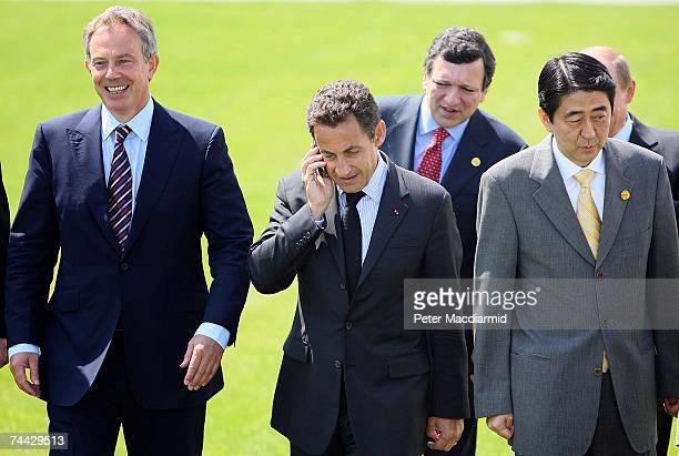 French President Nicolas Sarkozy takes a phone call as he stands with British Prime Minister Tony Blair , European Union President Manuel Barroso and...
